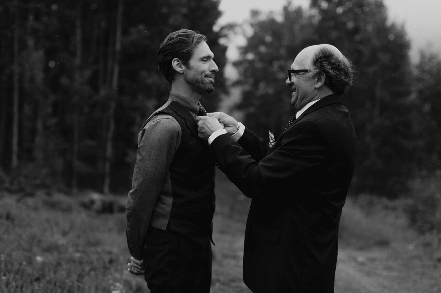 father helping his son tie his tie on a wedding day