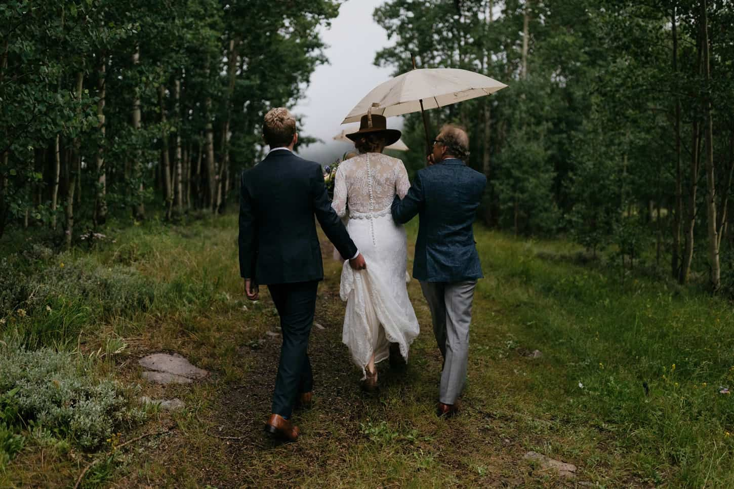 bride walking down the aisle in the rain on her wedding day in aspen