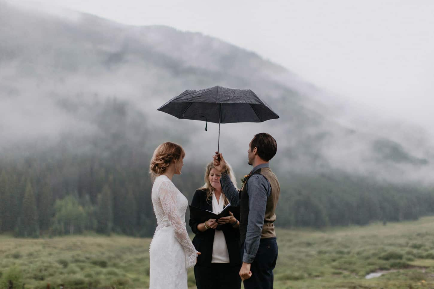 groom holds umbrella during wedding vows